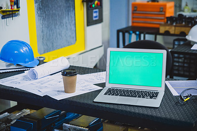 Buy stock photo Shot of an empty engineering workshop with blueprints and a laptop on the table