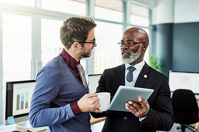 Buy stock photo Shot of two businessmen using a digital tablet together in an office