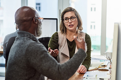 Buy stock photo Shot of a young businesswoman talking to a colleague in an office