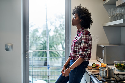 Buy stock photo Cropped shot of a young woman looking thoughtful at home
