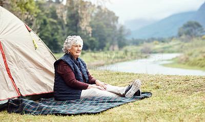 Buy stock photo Shot of a senior woman camping in the wilderness