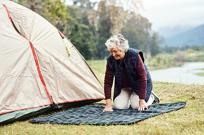 Buy stock photo Shot of a senior woman setting a picnic blanket alongside a tent while camping in the wilderness