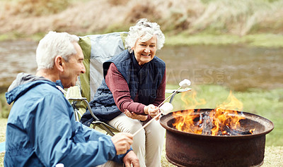 Buy stock photo Shot of a senior couple roasting marshmallows while camping in the wilderness