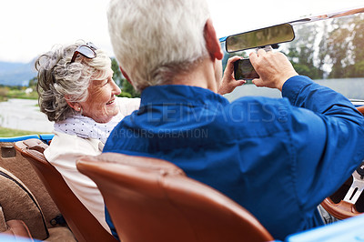 Buy stock photo Shot of a senior couple taking a selfie together while out on a road trip