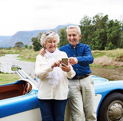 Buy stock photo Shot of a senior couple using a cellphone while out on a road trip
