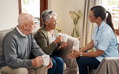 Buy stock photo Cropped shot of a happy senior couple sitting with their nurse and holding cups of coffee in their living room