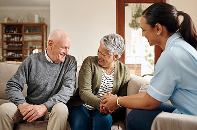 Buy stock photo Cropped shot of a happy senior couple sitting with their attractive young nurse aid in a nursing home