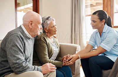 Buy stock photo Cropped shot of an attractive young nurse sitting with a senior couple in the living room of a nursing home