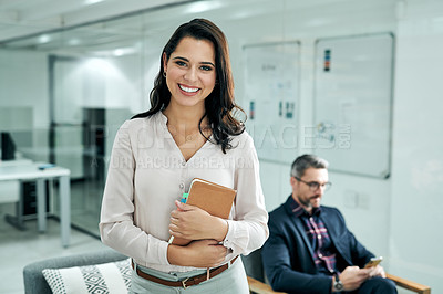 Buy stock photo Cropped shot of an attractive young businesswoman standing in the office while her male coworker sits behind her
