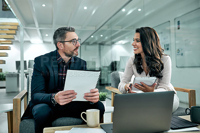 Buy stock photo Cropped shot of two businesspeople sitting in the office and using paperwork and technology during a meeting