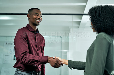 Buy stock photo Cropped shot of two young business colleagues standing in the office together and shaking hands after a meeting