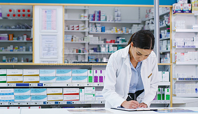 Buy stock photo Shot of a young pharmacist writing notes while working in a chemist
