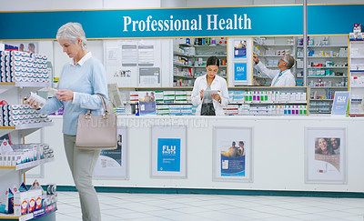 Buy stock photo Shot of pharmacists working and customers shopping in a chemist