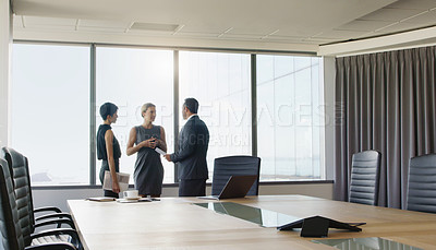 Buy stock photo Cropped shot of a diverse group of businesspeople standing in a boardroom together and having a discussion