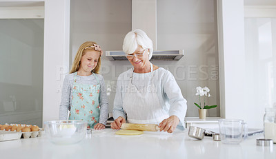 Buy stock photo Shot of an adorable little girl baking with her grandmother in their kitchen at home