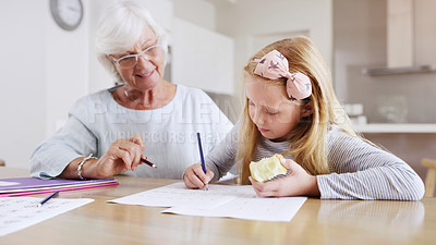 Buy stock photo Shot of a grandmother helping her little granddaughter with her school work at home