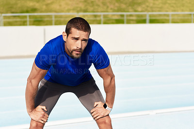 Buy stock photo Cropped portrait of a handsome young male athlete down on his haunches after a workout at the track