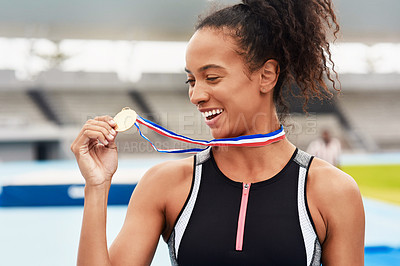 Buy stock photo Cropped shot of an attractive young female athlete posing with her gold medal out on the track