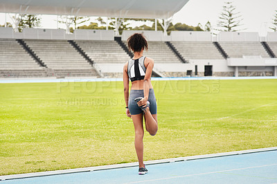 Buy stock photo Rearview shot of an attractive young female athlete warming up at the track