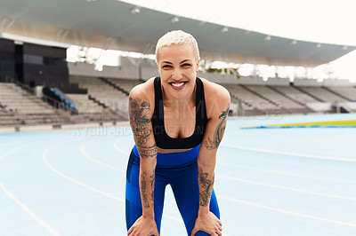 Buy stock photo Cropped portrait of an attractive young female athlete down on her haunches after a workout at the track