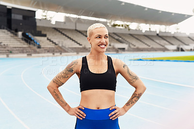 Buy stock photo Cropped shot of an attractive young female athlete standing with her hands on her hips out on the track