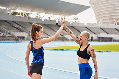 Buy stock photo Cropped shot of two attractive young female athletes high fiving while running along the track