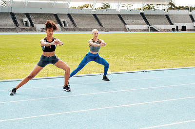 Buy stock photo Full length shot of two young attractive athletes standing together and holding side lunges outside on a running track
