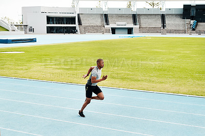 Buy stock photo Full length shot of a handsome young athlete running a track field alone during an outdoor workout session