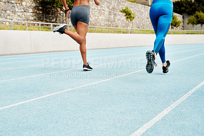 Buy stock photo Cropped shot of two unrecognizable athletes running along a track field alone during an outdoor workout session