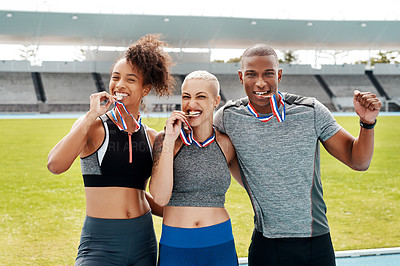 Buy stock photo Cropped portrait of a diverse group of athletes standing together and biting their medals after winning a running race