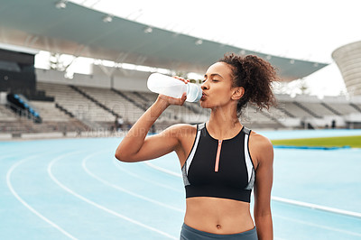 Buy stock photo Cropped shot of an attractive young athlete standing alone and drinking water during an outdoor training session alone