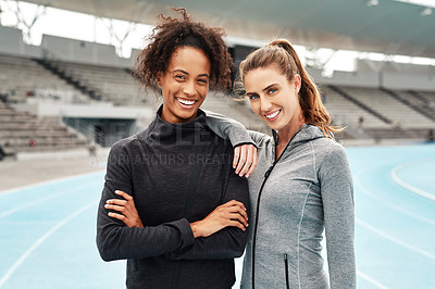 Buy stock photo Cropped portrait of two attractive young athletes standing together after a run on a track field during a training session