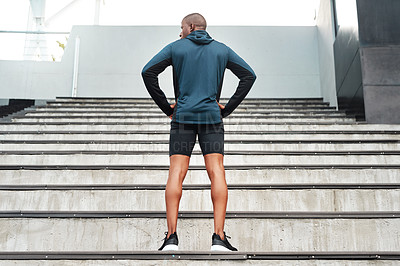 Buy stock photo Rearview shot of an unrecognizable young athlete standing akimbo before running up a flight of stairs during a workout