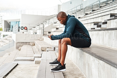 Buy stock photo Full length shot of a handsome young athlete sitting alone and texting on his cellphone after an outdoor training session