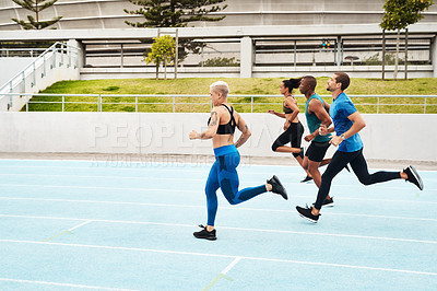 Buy stock photo Full length shot of a diverse group of athletes racing each other during an outdoor track and field workout session