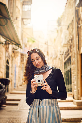 Buy stock photo Shot of a young woman taking photographs with a camera while exploring a town in Israel