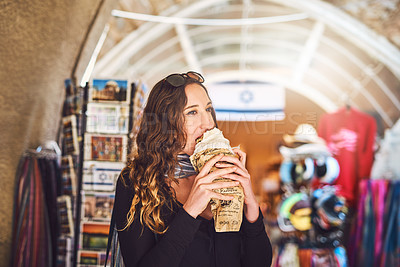 Buy stock photo Shot of a young woman eating a snack at a local market stall