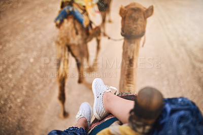 Buy stock photo Cropped shot of a woman riding on a camel in a desert