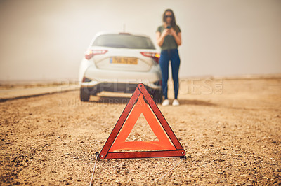 Buy stock photo Shot of an emergency warning triangle with a woman and her broken down car in the background
