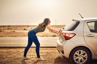Buy stock photo Shot of a young woman pushing her car along the road after breaking down