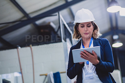 Buy stock photo Cropped shot of a focused female engineer wearing safety gear while doing an inspection on machinery inside of a workshop