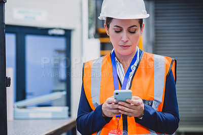 Buy stock photo Cropped shot of a carefree female engineer texting on her cellphone while wearing protective gear inside of a workshop during the day