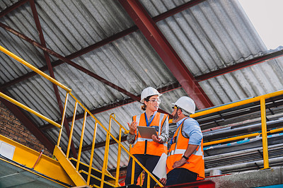 Buy stock photo Cropped shot of two confident engineers having a discussion together while standing on a flight of stairs