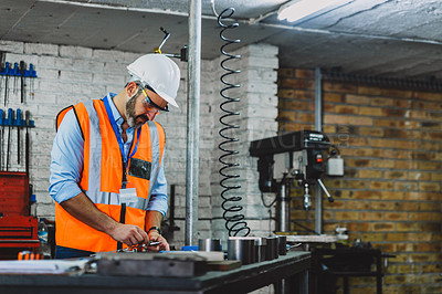Buy stock photo Cropped shot of a focused male engineer busy on a workbench inside of a workshop during the day
