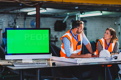 Buy stock photo Cropped shot of two engineers working together on blueprints while making use of a computer inside of a workshop
