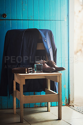 Buy stock photo Shot of a groom's suit, belt, shoes and perfume in a room on his wedding day
