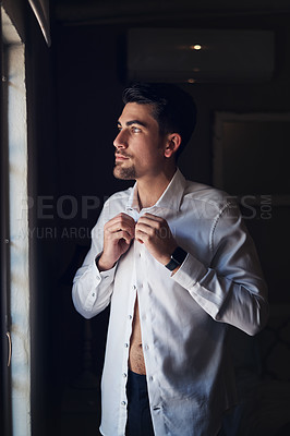 Buy stock photo Shot of a handsome young man getting dressed on his wedding day