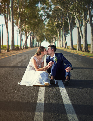 Buy stock photo Shot of a happy young couple sitting on a country road and kissing on their wedding day