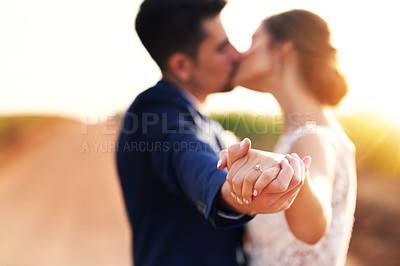 Buy stock photo Shot of a happy young couple dancing and kissing outdoors on their wedding day