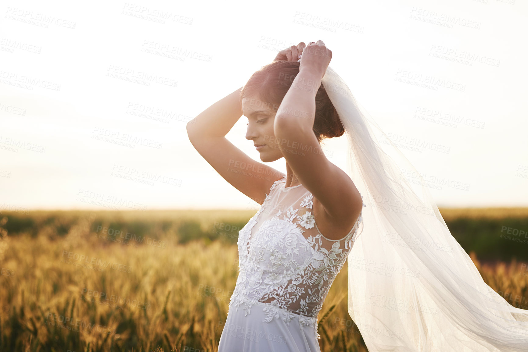 Buy stock photo Shot of a beautiful young bride standing in a field on her wedding day